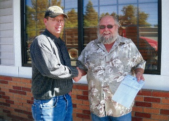IAM Local Lodge 509 member Corey Martin, right, receives disaster relief check from Local Chairman Gary Whitmer. Martin, of Minot, ND, suffered extensive loss from the record-setting flooding earlier this summer.