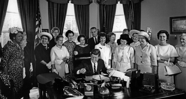 Surrounded by top women leaders, President John F. Kennedy signed the Equal Pay Act into law on June 10, 1963. The act made it illegal for employers to pay women and men different wages for the same work. (Credit: Abbie Rowe, White House Photographs. Courtesy of John F. Kennedy Presidential Library and Museum, Boston)